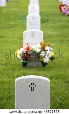 Headstones and flowers mark the graves of fallen soldiers at Fort Logan National Cemetery in Colorado (shallow depth of field). - stock photo