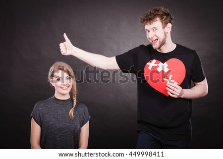 Heal love concept. Couple woman and man holding two halves of broken heart fixed with plaster bandage going to be joined in one.  - stock photo