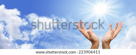 Healer's hands outstretched with bright sunburst above on a blue sky and fluffy cloud background - stock photo