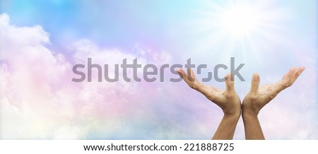 Healer's hands outstretched with sunburst above on a soft multicolored cloud background banner - stock photo