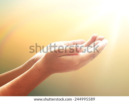 Healing Amazing Light - Human healer with hands open palm up surrounded by a rainbow and ray white light. Praying hand over blurred sunset background. - stock photo