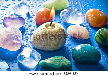 healing gemstones with a candle over blue background with drops of water - stock photo