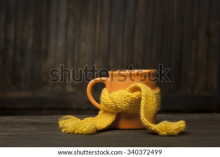 Healing glass of tea in a scarf on a wooden background - stock photo