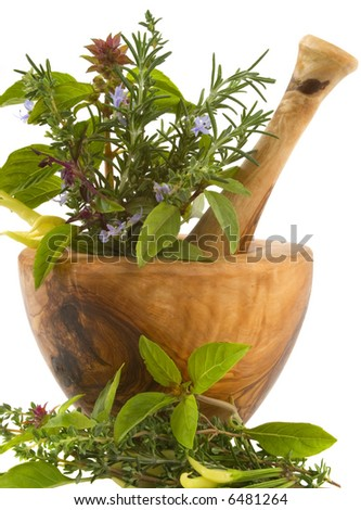 Healing herbs and edible flowers (hand carved olive tree mortar and pestle) - stock photo