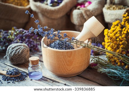 Healing herbs in hessian bags, wooden mortar with lavender flowers, bottles with tincture, herbal medicine. Selective focus. - stock photo