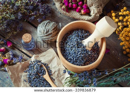 Healing herbs, wooden mortar with lavender, bottles of tincture, herbal medicine. Top view. - stock photo