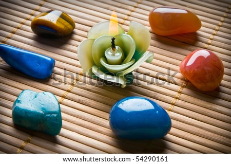 healing stones in circle with beautiful candle in form of flower on bamboo - stock photo