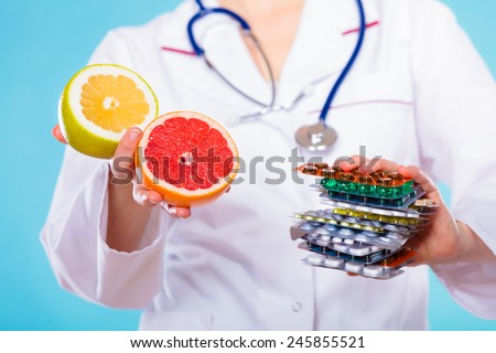Health and balanced diet concept. Choice between two sources of vitamins - pills or fruits. Medical doctor offering chemical and natural vitamins, holding stack of drugs and grapefruits on blue. - stock photo