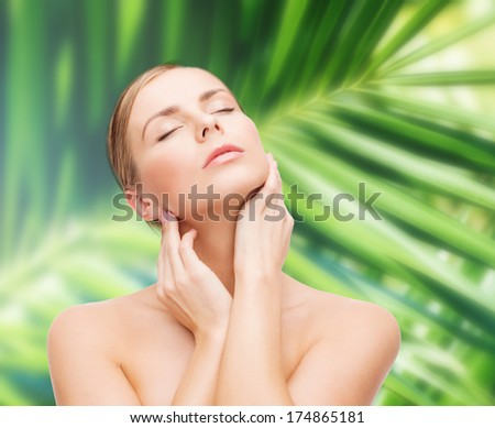 health and beauty concept - beautiful young woman touching her face with closed eyes