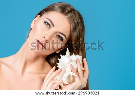 Health and beauty concept. Beautiful young woman with clean fresh skin posing with seashell. Skincare, bodycare. Spa. Sea vacation. - stock photo