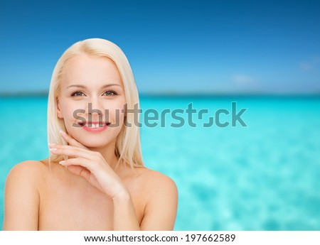 health and beauty concept - face and hands of beautiful woman