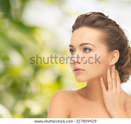 health and beauty concept - face and hands of beautiful woman with updo - stock photo