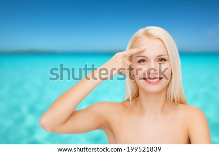 health and beauty concept - face of beautiful woman touching her forehead