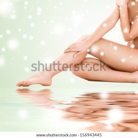 health and beauty concept - healthy naked woman legs over green background - stock photo