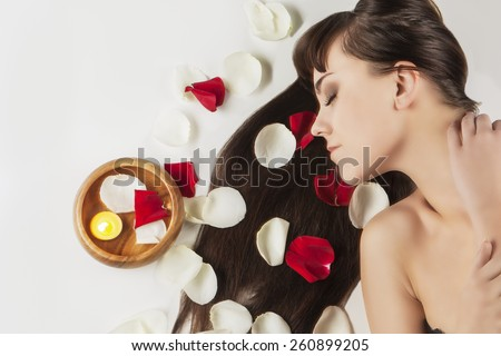 Health and Beauty Concept: Portrait of Relaxing Caucasian Female With Soft Silky Skin and Long Dark Hair.Rose Leafs and Wooden Bowl Are Used.Horizontal Image Composition - stock photo