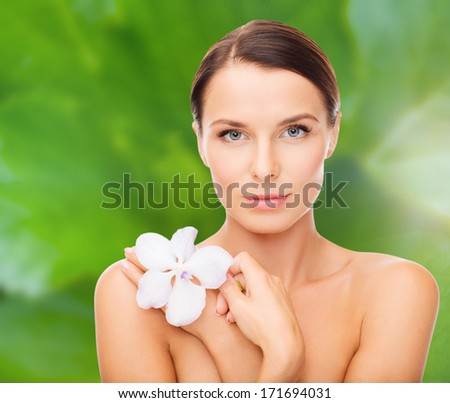 health and beauty concept - relaxed woman with orchid flower