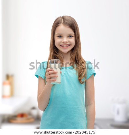 health and beauty concept - smiling little girl with glass of milk - stock photo