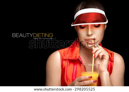 Health and Beauty Dieting. Stylish Young Sporty Woman, Wearing Transparent PVC Sun Visor and Fashion Sleeveless Shirt, Sipping a Glass of Fresh Orange Juice. Isolated on Black Background. - stock photo