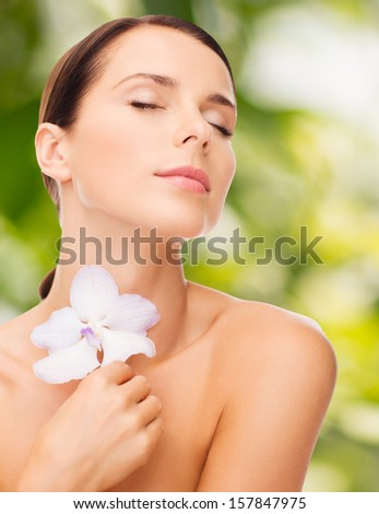 health and beauty, eco, bio, nature concept - relaxed woman with orhid flower