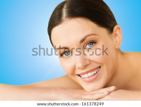 health and beauty, resort and relaxation concept - beautiful smiling woman in spa salon lying on the massage desk - stock photo