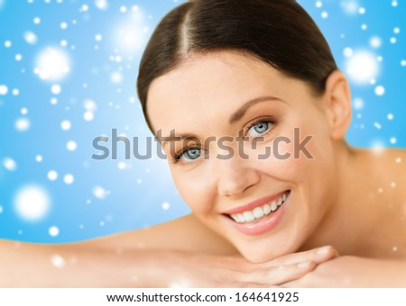 health and beauty, resort and relaxation concept - beautiful smiling woman in spa salon lying on the massage desk