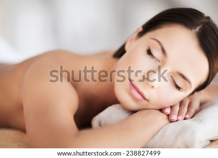 health and beauty, resort and relaxation concept - beautiful woman with closed eyes in spa salon lying on the massage desk - stock photo
