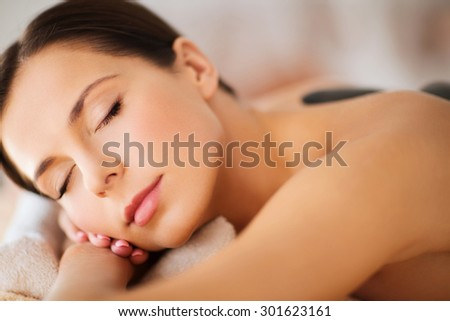 health and beauty, resort and relaxation concept - beautiful woman with closed eyes in spa salon with hot stones - stock photo