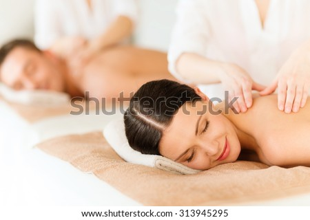 health and beauty, resort and relaxation concept - couple in spa salon getting massage - stock photo
