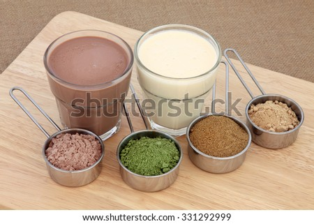 Health and body building food powder supplements and drinks with chocolate whey, wheat grass, pomegranate and maca root, left to right, with protein shakes. - stock photo