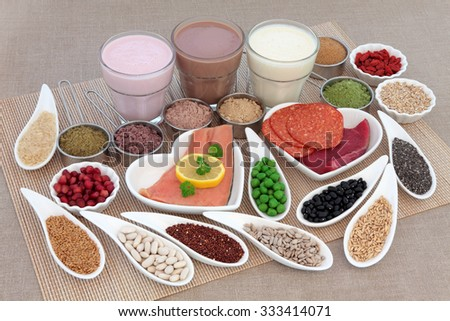 Health and body building high protein food of meat and fish, nuts, pulses, supplement powders, vegetables, fruit and smoothie juice drinks over bamboo and hessian background. - stock photo