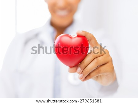 health and charity concept - close up of woman hand holding heart - stock photo