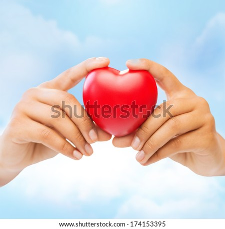 health and charity concept - closeup of female hands holding heart