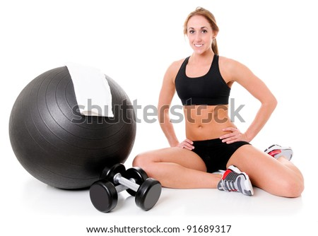 Health and Fitness woman in gym outfit with a Pilates ball, towel and weights - stock photo