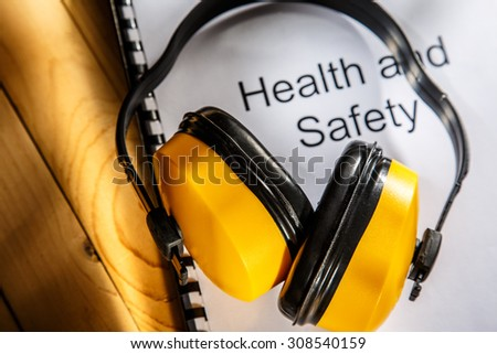 Health and safety register with earphones on wood - stock photo