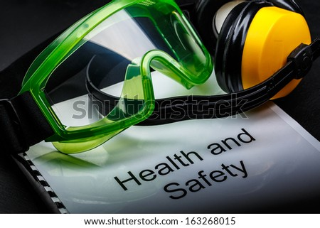 Health and safety register with goggles and earphones - stock photo