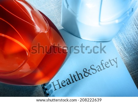 Health and safety with red and white helmets - stock photo