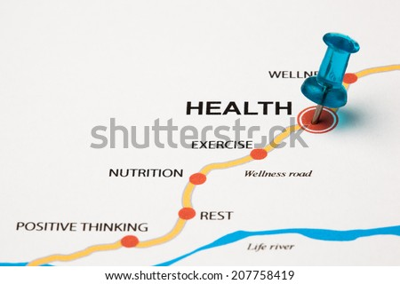 Health as target in the wellness road. Conceptual image where the cities are the principles that lead to the health target. Selective focus on the thumbtack. - stock photo
