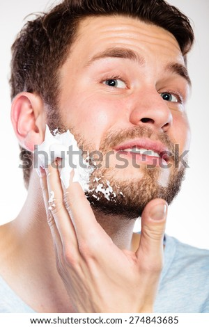 Health beauty and skin care concept. Closeup young bearded man with foam on face preparing to shave, guy shaving