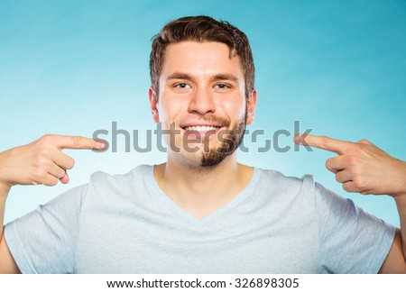 Health beauty and skin care concept. Handsome young man with half shaved and half bearded face looking at camera pointing on blue - stock photo