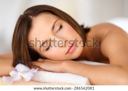 health, beauty, resort and relaxation concept - beautiful woman in spa salon lying on the massage desk - stock photo