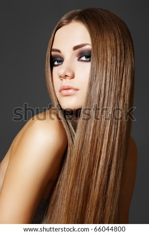 Health, beauty, wellness, haircare, cosmetics and make-up. Beautiful fashion hairstyle. Woman model with shiny straight long hair and evening make-up. - stock photo