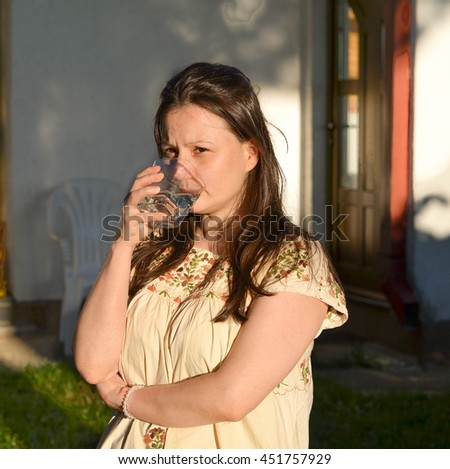 Health care and proper hydration -young woman drinking water during hot summer day, outdoors. - stock photo