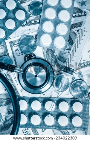 Health care cost - Stethoscope,pills and syringe over a stack of dollars toned in blue - stock photo