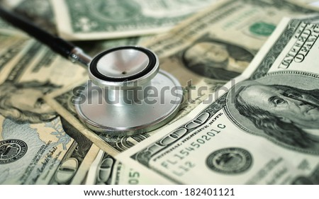 health care costs - Stethoscope on money background  - stock photo