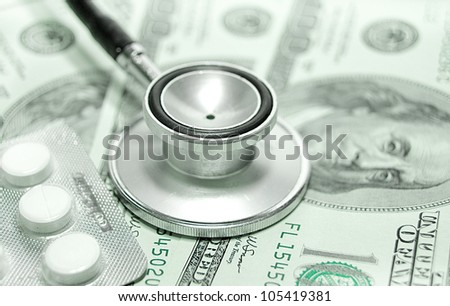 health care costs - Stethoscope on money background and pills - stock photo