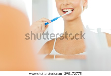 health care, dental hygiene, people and beauty concept - close up of smiling young woman with toothbrush cleaning teeth and looking to mirror at home bathroom - stock photo