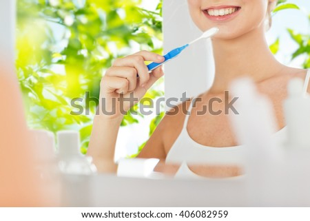 health care, dental hygiene, people and beauty concept - close up of smiling young woman with toothbrush cleaning teeth and looking to mirror at home bathroom over green natural background - stock photo