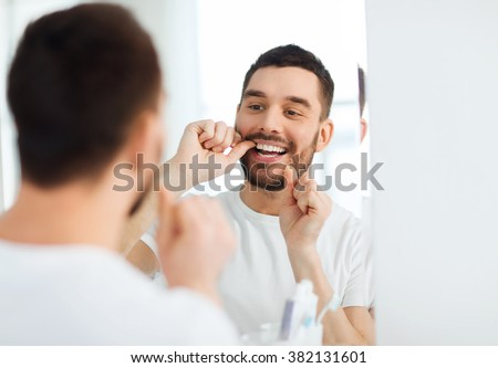 health care, dental hygiene, people and beauty concept - smiling young man with floss cleaning teeth and looking to mirror at home bathroom - stock photo