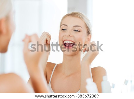 health care, dental hygiene, people and beauty concept - smiling young woman with floss cleaning teeth and looking to mirror at home bathroom - stock photo