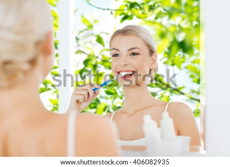 health care, dental hygiene, people and beauty concept - smiling young woman with toothbrush cleaning teeth and looking to mirror at home bathroom over green natural background - stock photo